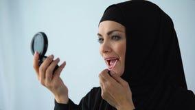 Женщина в hijab прикладывая зеркало руки удерживания губной помады, женственность и красоту сток-видео