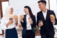 Женщина в hijab при ее коллеги есть гамбургер и выпивая кофе Стоковые Фото