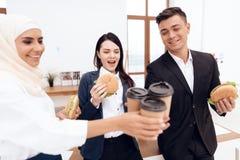 Женщина в hijab при ее коллеги есть гамбургер и выпивая кофе Стоковое фото RF