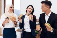 Женщина в hijab при ее коллеги есть гамбургер и выпивая кофе Стоковое Изображение RF