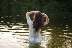Женщина в nightie купает в реке стоковое изображение