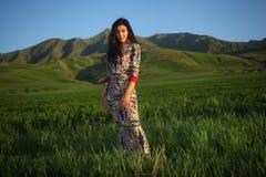 Женщина в platte на заходе солнца в поле на предпосылке гор Стоковая Фотография RF