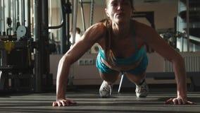 Женщина в sportswear делает нажим-поднимает в спортзале сток-видео