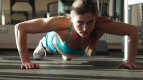 Женщина в sportswear делает нажим-поднимает в спортзале акции видеоматериалы