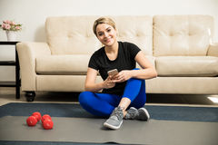 Женщина в sporty обмундировании используя smartphone Стоковое Фото