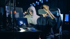 Женщина в VR-стеклах и ее мужской коллега рубят акции видеоматериалы