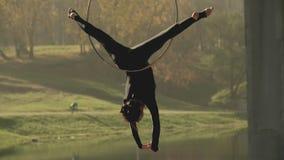 Женщина гимнастики воздуха выполняет фокусы акробатики на воздушном обруче в замедленном движении акции видеоматериалы