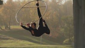 Женщина гимнастики воздуха выполняет фокусы акробатики на воздушном обруче в замедленном движении сток-видео