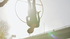Женщина гимнастики воздуха выполняет фокусы акробатики на воздушном обруче на восходе солнца видеоматериал