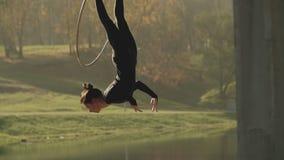 Женщина гимнастики воздуха выполняет фокусы акробатики на воздушном обруче в замедленном движении видеоматериал