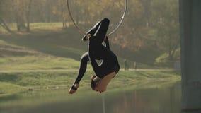 Женщина гимнастики воздуха выполняет фокус акробатики на воздушном обруче Гибкий брюнет акции видеоматериалы
