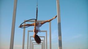 Женщина гимнастики воздуха выполняет фокусы акробатики на воздушном обруче видеоматериал