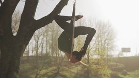 Женщина гимнастики выполняет фокусы акробатики на воздушном обруче Гибкий брюнет видеоматериал