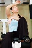 женщина гимнастики прибора сидя утомленная стоковая фотография