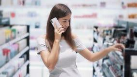 Женщина говорит по телефону и выбирает маникюр в магазине косметик, замедленном движении акции видеоматериалы