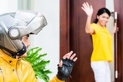 Женщина говоря до свидания к ей boyfrined нося шлем стоковое фото