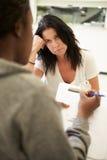 Женщина говоря к консультанту который принимает примечания стоковые фотографии rf
