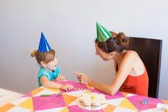 Женщина говоря к маленькой девочке на вечеринке по случаю дня рождения Стоковое Изображение RF