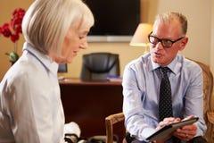 Женщина говоря к мужскому консультанту используя плату цифров Стоковое Фото