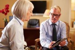 Женщина говоря к мужскому консультанту используя плату цифров Стоковые Фотографии RF