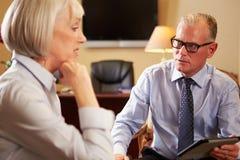Женщина говоря к мужскому консультанту используя таблетку цифров Стоковые Изображения RF