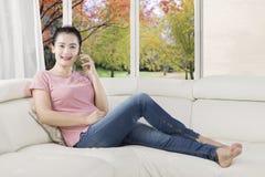 Женщина говоря на мобильном телефоне на кресле Стоковое фото RF