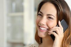 Женщина говоря на мобильном телефоне дома