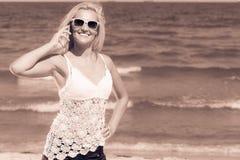 Женщина говоря на передвижном сотовом телефоне взморьем Стоковые Изображения