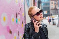 Женщина говоря на склонности smartphone против красочной стены граффити в Нью-Йорке, США Стоковые Изображения RF