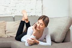 Женщина говоря на сотовом телефоне лежа на кресле Стоковые Изображения