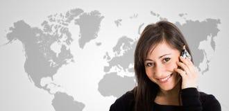 Женщина говоря на телефоне перед картой мира стоковые фото