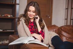 Женщина говоря на телефоне и читая кассету Стоковая Фотография RF