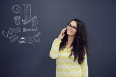 Женщина говоря на телефоне перед предпосылкой с вычерченными диаграммами дела Стоковые Фото