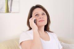 Женщина говоря на телефоне сидя на софе Стоковые Фото