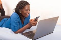 Женщина говоря по телефону в кровати перед ноутбуком стоковая фотография rf