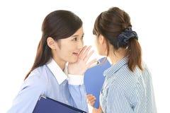 Женщина говоря секрет к ее другу стоковые фотографии rf