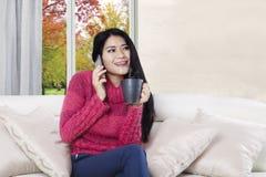 Женщина говоря телефоном на кресле Стоковая Фотография RF