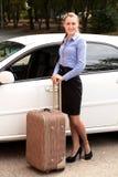 Женщина готовя белый автомобиль с большим чемоданом стоковые изображения