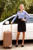 Женщина готовя белый автомобиль с большим чемоданом стоковое изображение rf