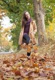 Женщина гуляет в листья осени Стоковая Фотография