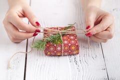 Женщина дает обернутую настоящим моментом бумагу ремесла на постаретом деревянном столе, коробке праздничного подарка Copyspace о Стоковые Фото