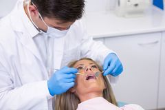 Женщина дантиста рассматривая на зубоврачебной клинике Стоковые Фото