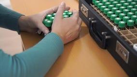 Женщина двигает медицинские бутылки и переносит их из случая Рассчитывает заново косметическую смесь сток-видео