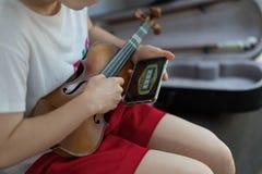 Женщина девушки настраивает ее телефон пользы скрипки электрический стоковое фото rf