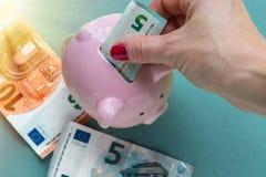 женщина дег банка piggy кладя стоковая фотография rf