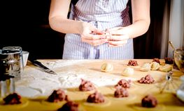 Женщина делает вареники дома на кухонном столе, конце вверх Стоковые Фотографии RF
