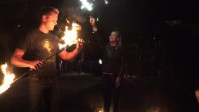 Женщина делает круг с пирофакелом огня холодным вечером 4K видеоматериал