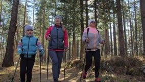 Женщина делает нордический идти в природу Девушки и дети используют trekking ручки и нордические поляков, рюкзаки перемещения сем видеоматериал
