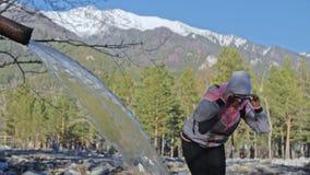 Женщина делает нордический идти в природу, питьевую воду от минерального источника Девушки используют trekking ручки и нордически акции видеоматериалы