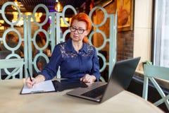 Женщина делает примечания в таблетке с бумагами на таблице с компьтер-книжкой в кафе Стоковые Фотографии RF